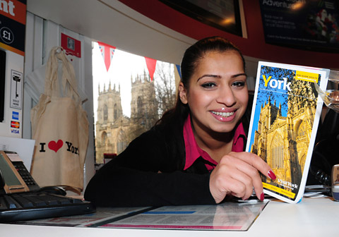Sam Farooq, at her desk at the Visit York Information Centre, with York Minster through the window behind her