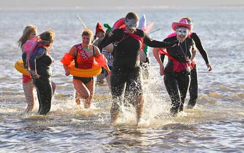 Swimmers plunge into the chilly North Sea at Scarborough's South Bay to ra