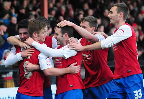 Midfielder Paddy McLaughlin, far left, is mobbed after bagging City's second goal against Burton Albion yesterday