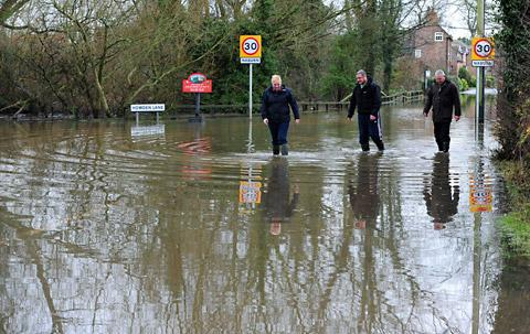 Three people make their way along a flooded road in Naburn