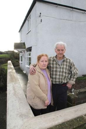Violet and Brian Coatsworth outside their house at Crakehill near Dalton which has been cut off by flood wate