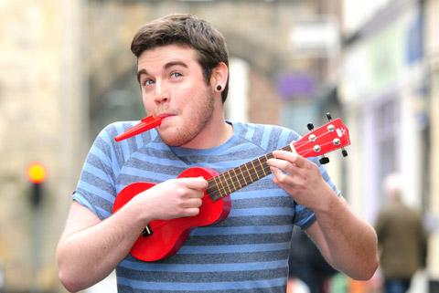 Miles Morrison, son of Steve Morrison, organiser of the York Ukulele Festival, plays a ukulele in Goodramgate, York