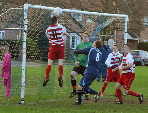 Malton & Norton's Kingsley Daffan, number 11, clears the ball over his own crossbar to safety, away from Haxby United dangerman Rich Burnett, number eight