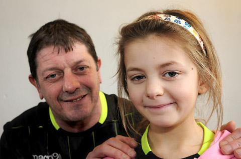 Millie Crick, eight, who has recovered from meningitis after eight days in hospital, with her father, Paul