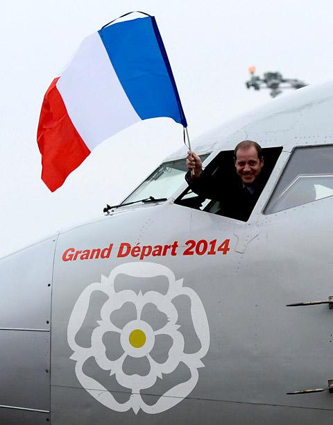 Tour de France Director Christian Prudhomme waves the French flag as he arrives for the 2014 Tour de France Yorkshire route announcement, at Leeds Bradford Airport