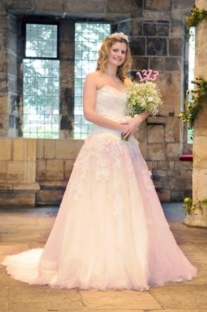 Melody Beavers, wedding and events co-ordinator, models a wedding dress at the Hospitium, which is discounting rate