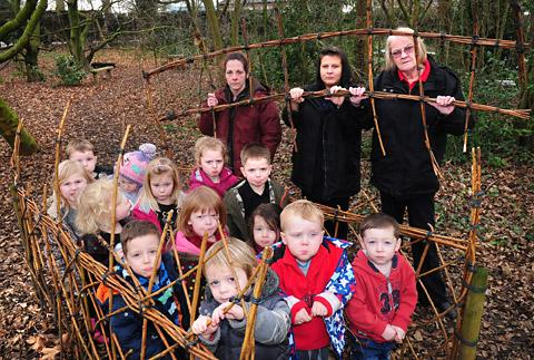 Ladybirds nursery staff Nina Simpson, Giouanna Gioiello and Nickey Beveridge with children inside the vandalised willow arch