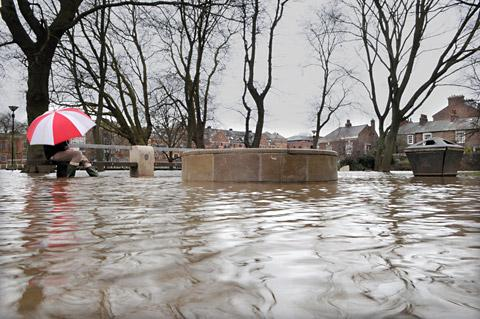 A man sits on a bench in the flooded Tower Gardens in York