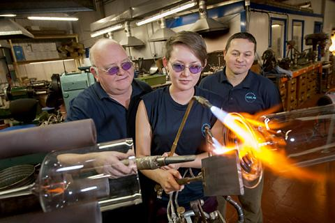 Eloise at work under the watchful eyes of head               glassblower Tony Mercer, left, and managing director Alex Davis, in YorLab's glassblowing factory based near York