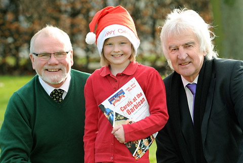 Young singer Lily Clayton with carol concert organiser Graham Bradbury, left, and musician Steve Cassidy