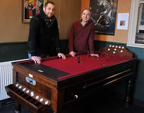 Mike Shalcross, right, and Jon Fulton with the 1930s bar billiards table at The Phoenix Inn.