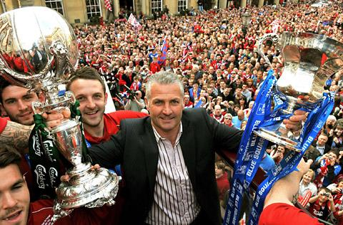 York City boss Gary Mills with the FA Trophy and play-off final cup during the club's open-top bus tour last May