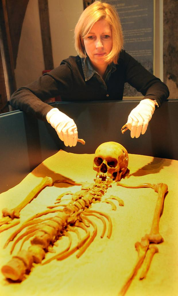 Osteoarchaeologist Malin Holst places a skeleton that died of leprosy in a display case for the York Archaeological Trust's Plague, Poverty And Prayer exhibition at Barley Hall