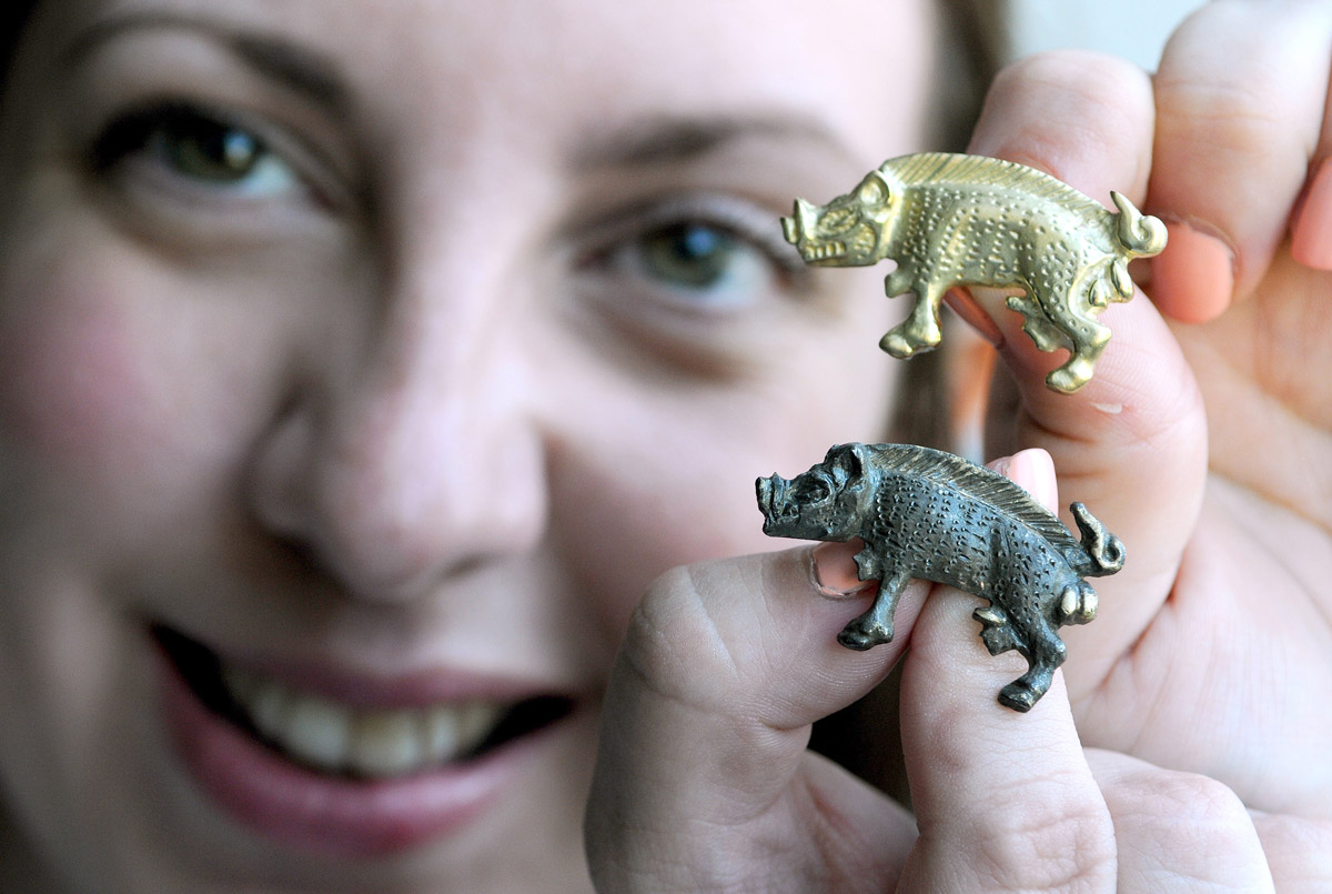 Natalie McCaul, the Yorkshire Museum's curator of archaeology, holds an original Richard III boar badge and the 18-carat gold replica