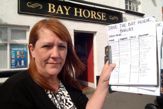 Bay Horse manager Alyson Griffiths with the petition launched last year to try and save the pub