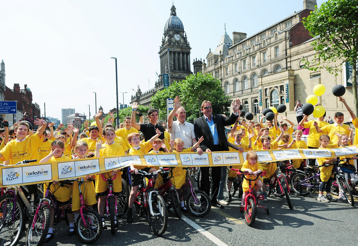 "Yorkshire's ""Pied Piper of Tourism"":  Gary Verity, wearing sunglasses, joins local schoolchildren on the Headrow in Leeds as part of the countdown to Le Grand Depart"