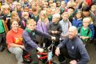 Luke Dorking, aged nine, is presented with his bike by Naomi Wells Smith, of Sustrans, and Piers Maffett, of Cycle Heaven, at Yearsley Grove School
