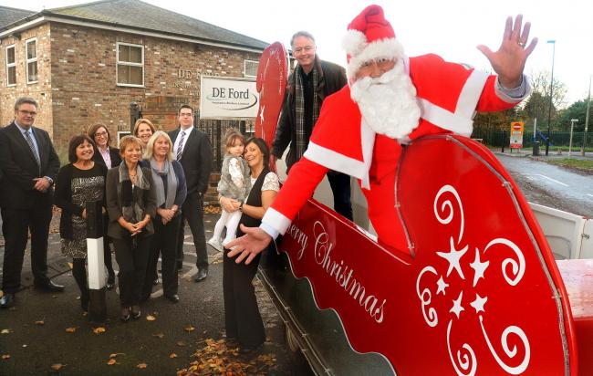 The Rotary Club of York Ainsty's new sleigh complete with Santa Claus and his helper, Steve Cluderay, with staff at D E Ford, in Poppleton Lane