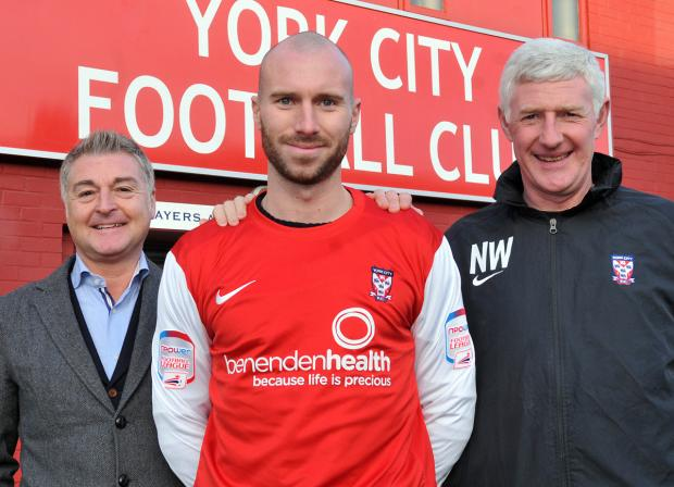 York City chairman Jason McGill, left, and manager Nigel Worthington, right, with new signing Russell Penn