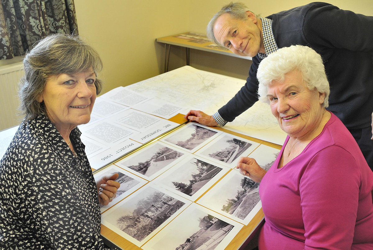 Members of the local history group, from left, Meg Ashbridge, Beryl Haigh and Peter Brown looking at some of the old photographs of the village