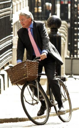 Former Government chief whip Andrew Mitchell arriving at Downing Street, London, on his bike
