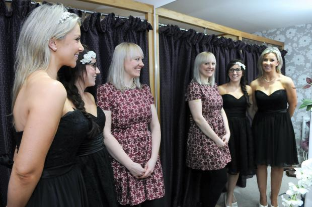 Win A Wedding competition bride-to-be Lauren Beevers (in patterned dress), looks into the mirror with bridesmaids Sarah Lacey and Robbie Wilson, at Wedding Belles and Beaus