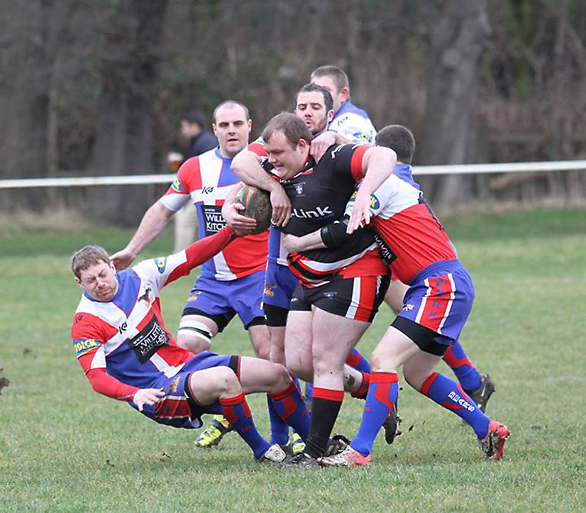 A posse of Sherburn players halt former Brotherton player Tom Bell as he drives the ball in for Wakefield City
