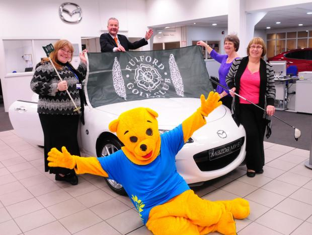 Hospice mascot Lenny Bear with Annie Keogh, Graham Keller of Mazda, Joan Foster and Fiona White of Fulford Golf Club