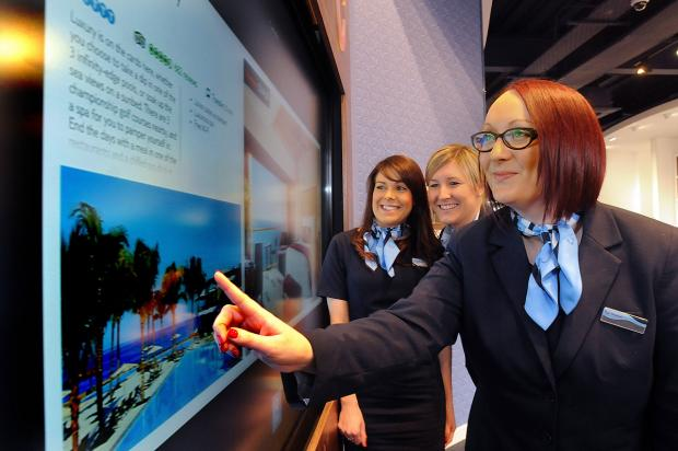 Thomson staff from left, Nicole Dawson, Lisa Appleton and manager Laura Heywood use the 84-inch touch screen at the new Thomson Travel Agents super store