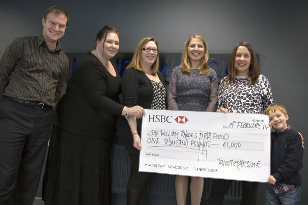 William Rhodes, next to his mum, Caroline, receives a cheque from staff from Trustmarque Solutions Limited