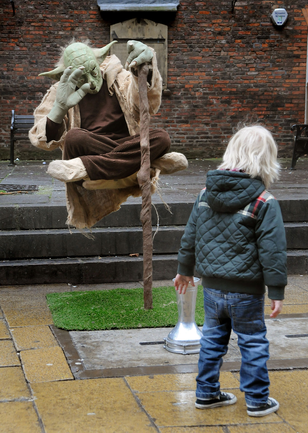 "The Yoda busker catches the attention of a young passerby as he ""levitates"" in Davygate, York."