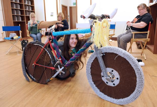 Cassandra Kilbride, foreground, adds some more knitting to a woolly bike with fellow knitters, from left, Charlotte Blacker, Diane Green and Rebecca Boldry, at York Designer Outlet