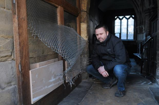 Graham White, of the Churches Conservation Trust, examines damage at Holy Trinity Church, Goodramgate, York, after thieves broke in
