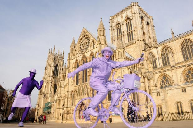 York Press: Pyramid Gallery owner Terry Brett tries out Purpleman's bike, chased by Purpleman, left, to promote the exhibition to help children in Syria