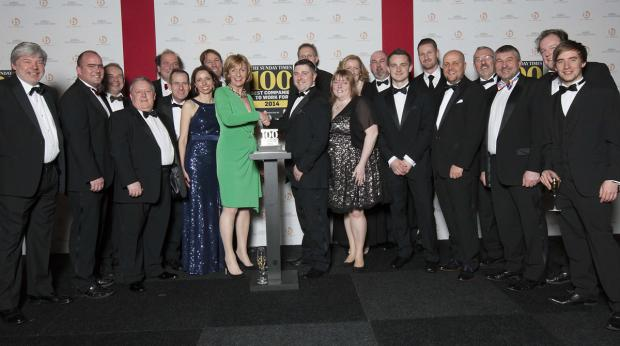 Lindum employees receiving their award from Karen Robinson of The Sunday Times at the awards dinner in London