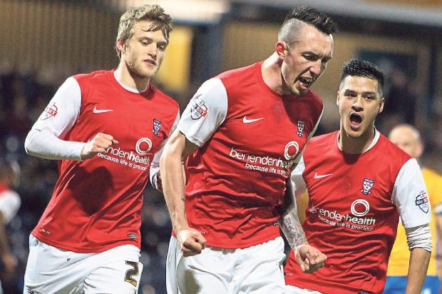 York City striker Ryan Bowman celebrates with team-mates Will Hayhurst, left, and Adam Reed, right, after giving his side the lead from the penalty spot against Mansfield Town at Field Mill in Sky Bet League Two. Picture: Gordon Clayton