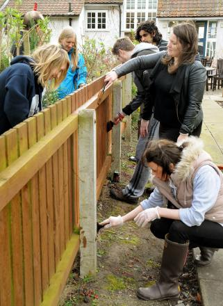 COMMUNITY SPIRIT: Volunteers from Benendon Health fence painting and gardening at the New Earswick Folk Hall. Picture: David Harrison
