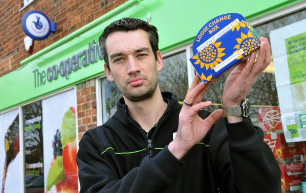 Manager Mark Porter with a similar charity box to the one stolen from his Co-op store in Broadway, Fulford.