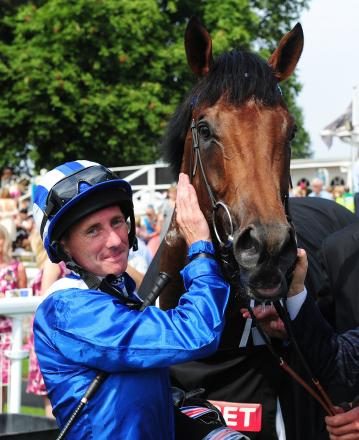 Jockey Paul Hanagan celebrates with Mukhadram after winning the Sky Bet York Stakes during the Music Showcase Weekend at York Racecourse, York.