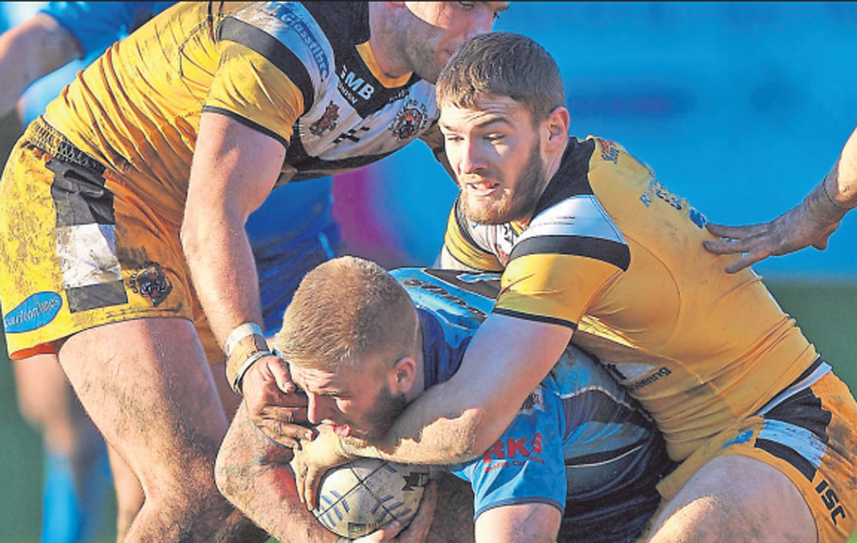 Ryan Backhouse, pictured being brought to ground by Andy Lynch and Daryl Clark during the Knights' pre-season friendly against Castleford, is returning to Huntington Stadium