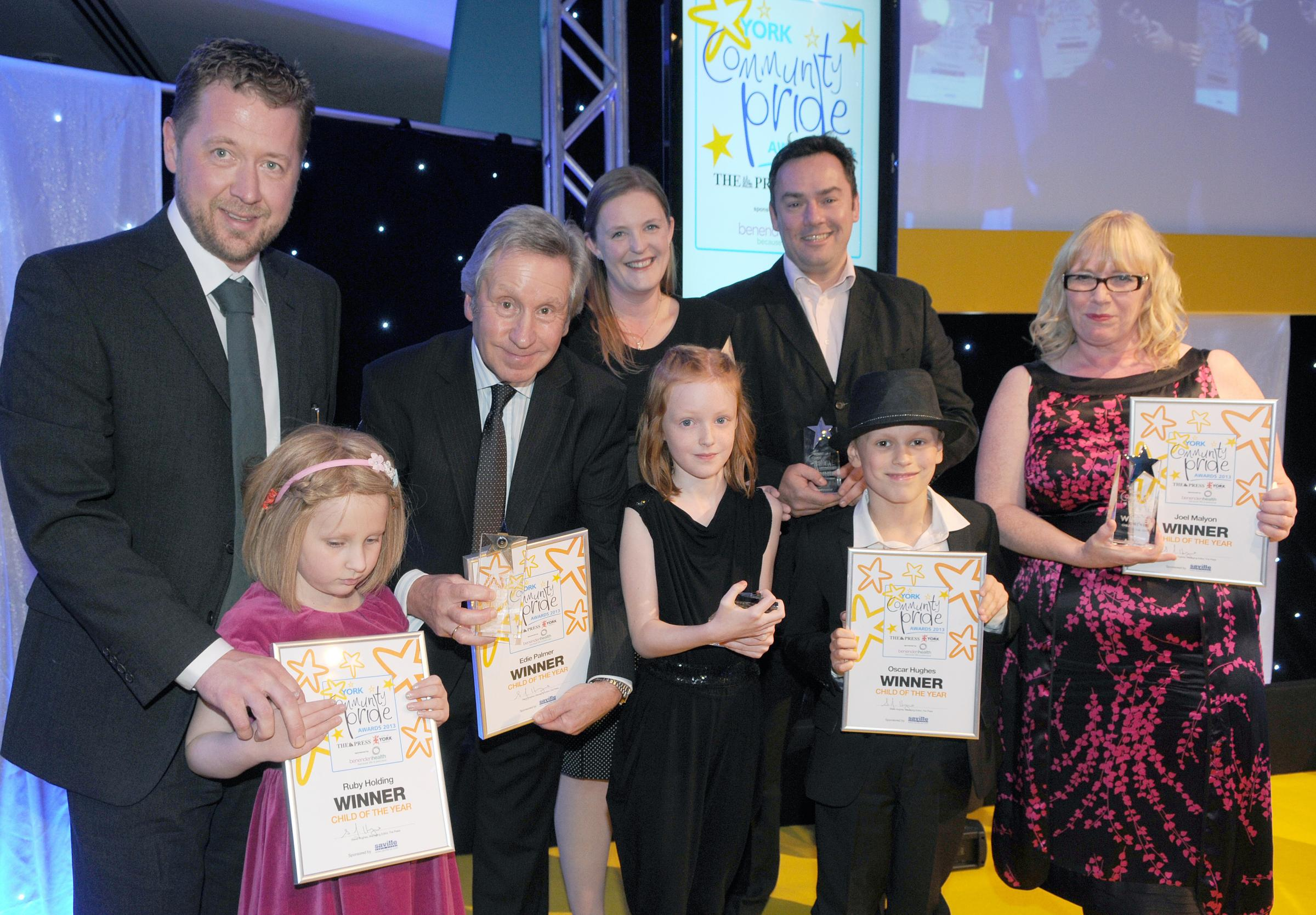 Edward Everard (third left), of Saville Audio Visual, with youngsters and parents on stage during the 2013 Child of the Year joint presentation.