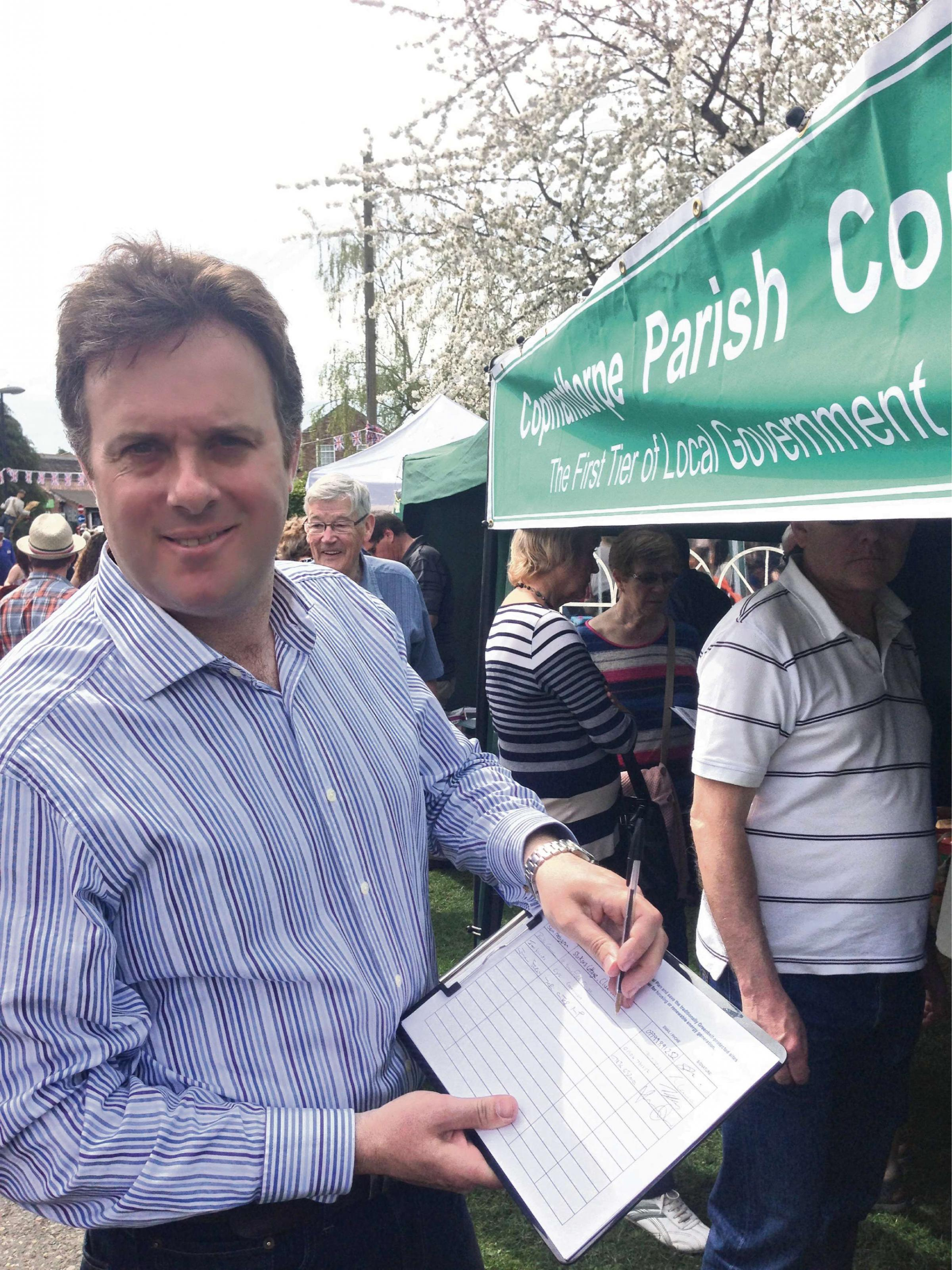 York Outer MP Julian Sturdy, pictured signing a residents' petition against the city's Local Plan, which includes dozens of potential wind farm sites
