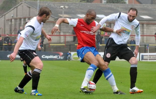York City striker Calvin Andrew, centre, tries to turn away from Accrington Stanley defender Nicky Hunt, right, on his full debut.