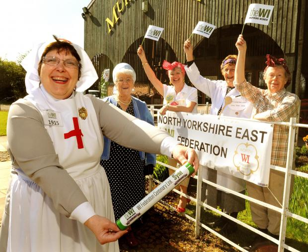 Members of the Womens Institute North Yorkshire East Federation dressed in wartime period costume to welcome the organisation's baton to the Yorkshire Museum of Farming at Murton Park as part of its national centenary tour of the country.