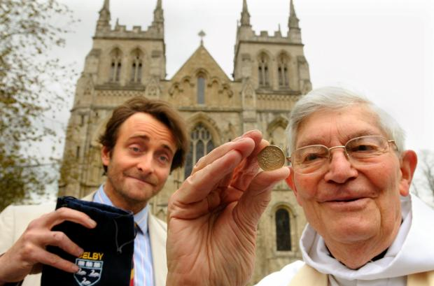 Tim FitzHigham, The Pittancer of Selby, presents Canon Roy Matthews, the former Vicar of Selby, with a pound coin, as is traditional after the Abbey's Maundy Thursday service.