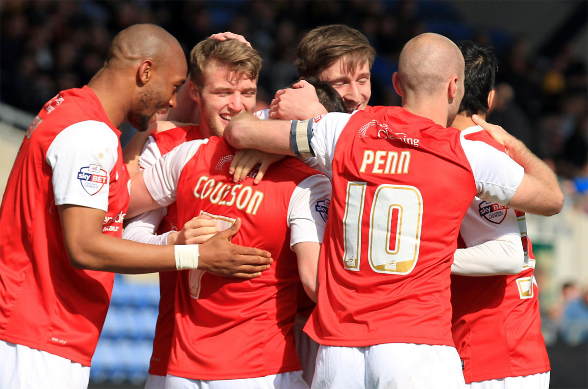 Michael Coulson is mobbed by his team-mates after netting the winner from the penalty spot at Oxford