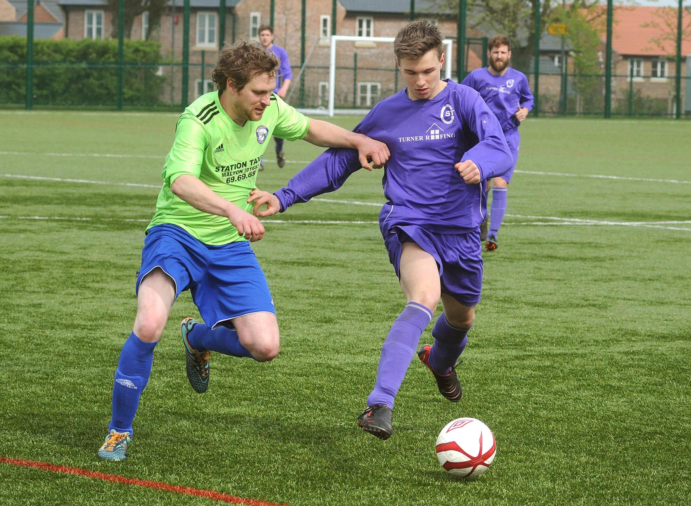 Brooklyn's Richard Webster, left, and St Clement's Dan Hickey, right, battle for possession in their York Minster Engineering Football League Senior Cup clash, which Brooklyn won 2-0 to advance to the semi-finals