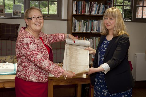 Cllr Sonia Crisp and Victoria Pierce unroll a new beginning for York Explore Libraries and Archives