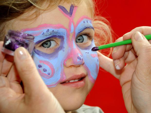 York Press: The finishing touches are made to a little girl's butterfly face-painting