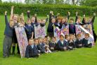 The young artists from St Aelred's school with their four sections of the giant mural which will be displayed on York's Knavesmire during the Tour de France
